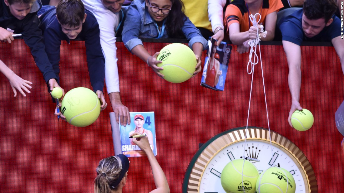 Sharapova signs autographs after winning a match at last  year's Australian Open. She later announced she had tested positive for banned drug meldonium and was banned for two years, later reduced to 15 months.