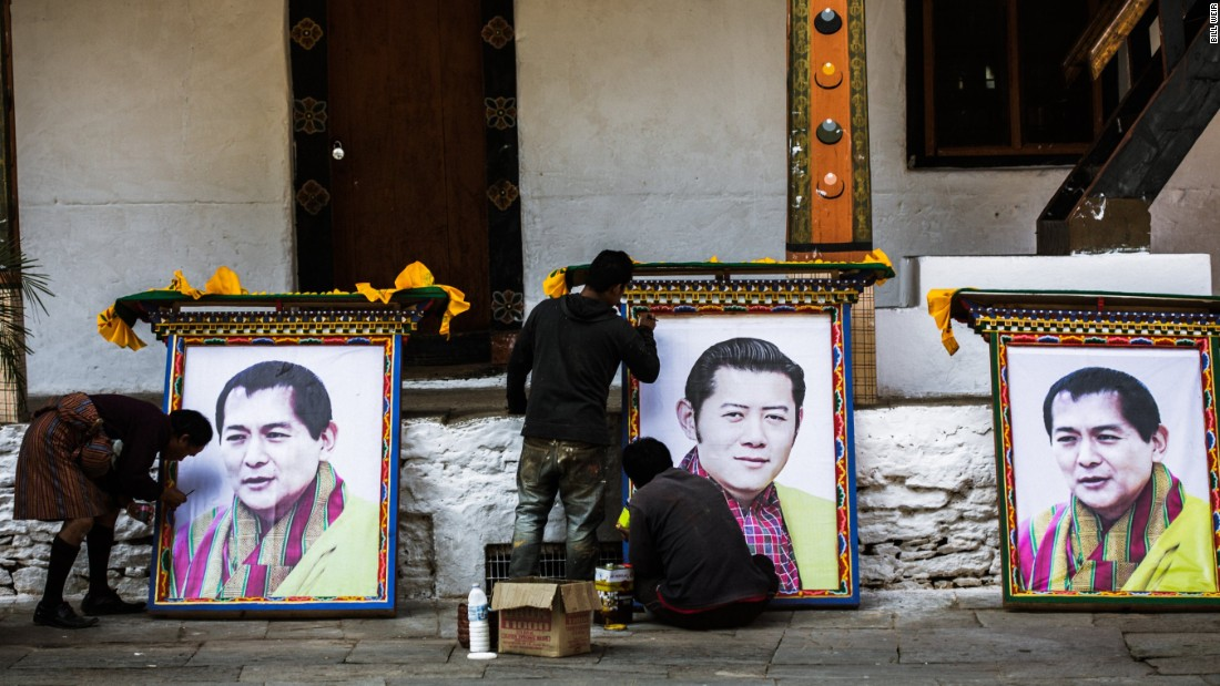 "Workers at the Punakha Dzong temple prepare portraits of Bhutan's fourth and fifth kings as part of the fourth king's 60th birthday celebration. Known as ""K4,"" Jigme Singye Wangchuk introduced democracy and the concept of Gross National Happiness."