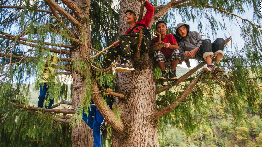 Children find a better vantage point at a music festival outside the capital city of Thimphu. Recent advances in technology have introduced Bhutanese artists, including a rapper inspired by Eminem, to more modern forms of music.
