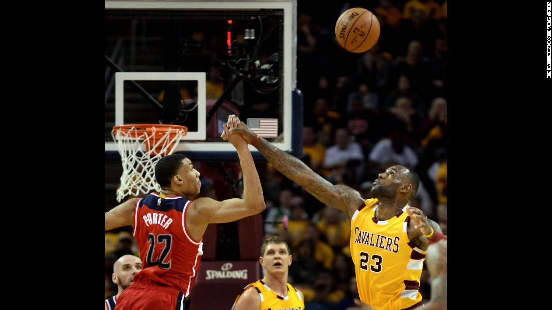 Otto Porter Jr. and LeBron James reach for a loose ball during an NBA game in Cleveland on Friday, March 4.