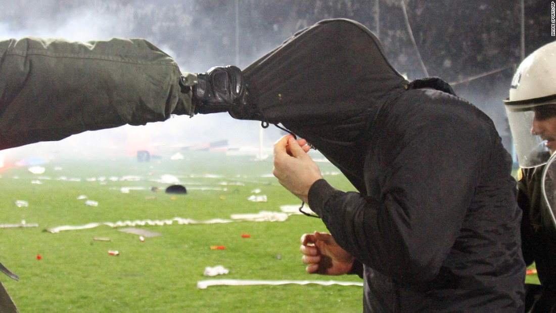 Riot police detain a fan during a Greek Cup soccer match in Thessaloniki on Wednesday, March 2. The semifinal match between Olympiakos and PAOK was stopped in the final minute after angry PAOK fans threw flares onto the field and clashed with police.