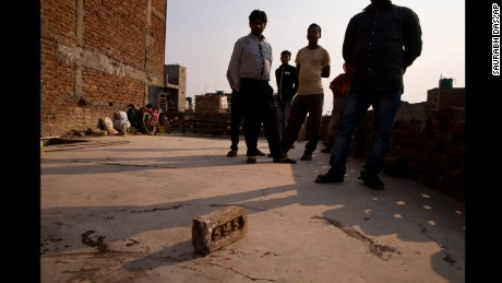 Relatives stand on the terrace of a house where a 15-year-old girl was set on fire after being raped.