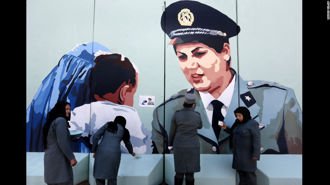 Police Officer Friba Hameed, second from right, helps paint a mural of herself outside the main gate of a police precinct in Kabul, Afghanistan, on March 8.