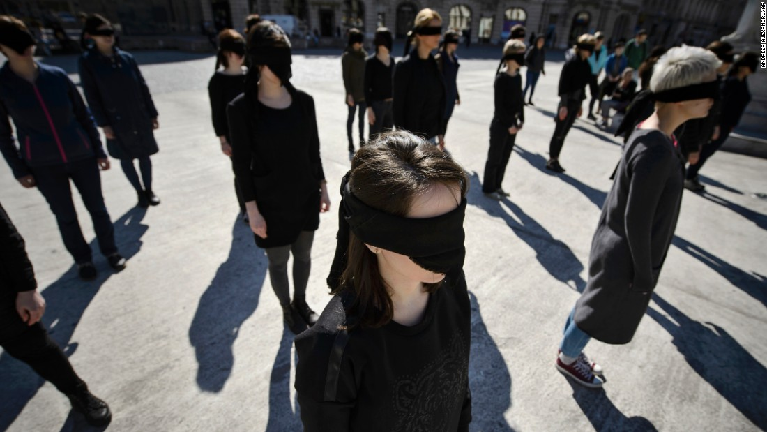 Activists stand blindfolded in Bucharest, Romania, during a March 8 performance honoring the history of feminist movements.