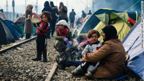 "A woman sits with a child on her laps by railway tracks at a makeshift camp at the Greek-Macedonian border near the Greek village of Idomeni where thousands of refugees and migrants are stranded on March 8, 2016.  European Union leaders on March 7 hailed a ""breakthrough"" in talks with Turkey on a deal to curb the migrant crisis but delayed a decision until a summit next week to flesh out the details of Ankara's new demands. More than one million refugees and migrants have arrived in Europe since the start of 2015 -- the majority fleeing the war in Syria -- with nearly 4,000 dying while crossing the Mediterranean. / AFP / DIMITAR DILKOFF        (Photo credit should read DIMITAR DILKOFF/AFP/Getty Images)"