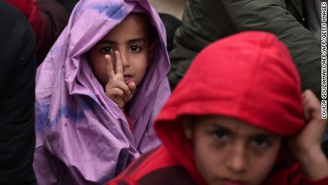 A young boy wrapped in a blanket to protect him from the rain gestures as migrants and refugees protest to call for the opening of the borders near the village of Idomeni where thousands of refugees and migrants are stranded on March 7, 2016.  EU leaders held a summit with Turkey's prime minister on March 7 in order to back closing the Balkans migrant route and urge Ankara to accept deportations of large numbers of economic migrants from overstretched Greece. / AFP / LOUISA GOULIAMAKI        (Photo credit should read LOUISA GOULIAMAKI/AFP/Getty Images)