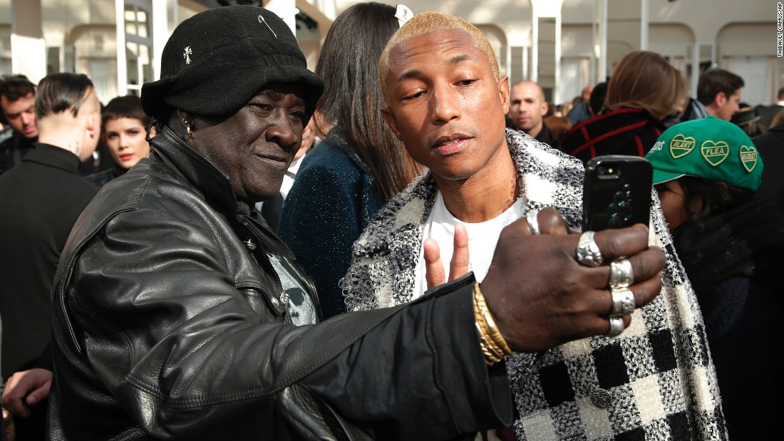 Musician Pharrell Williams, right, poses for a fan's selfie at a Chanel fashion show in Paris on Tuesday, March 8.