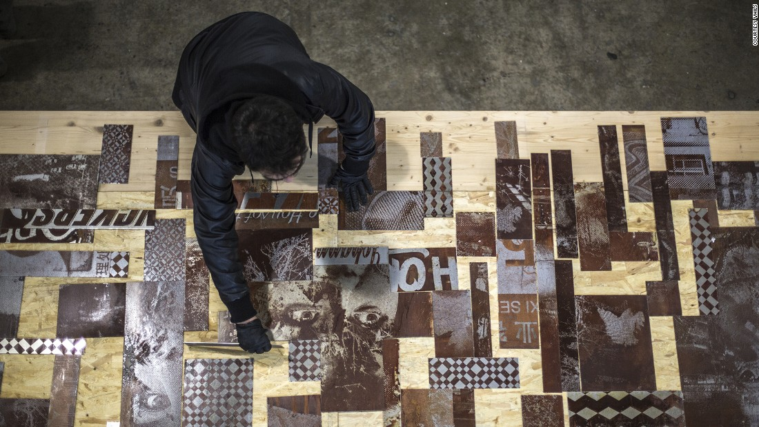 Vhils composes a piece of art using metal plates with images of commercial street signs, buildings and text gathered from around Hong Kong. By juxtaposing these images with portraits he points to the way in which the environment of a city impacts and shapes its inhabitants.