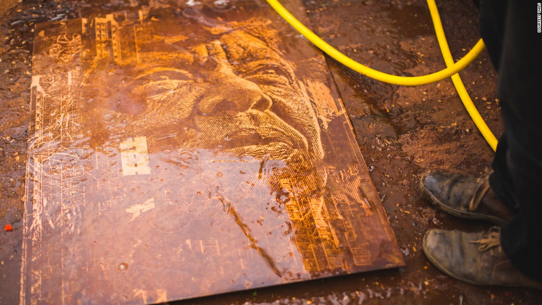 An etched metal plate being washed after an acid bath.