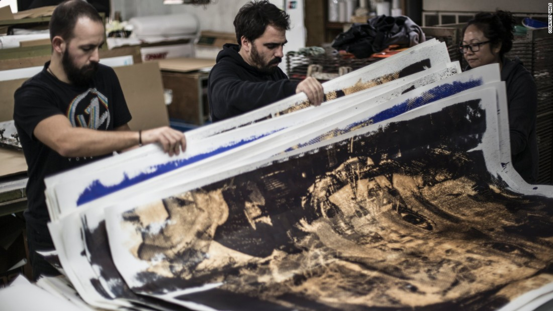 Vhils and his studio manager checking silkscreen prints at a factory in Hong Kong ahead of his exhibition Debris.