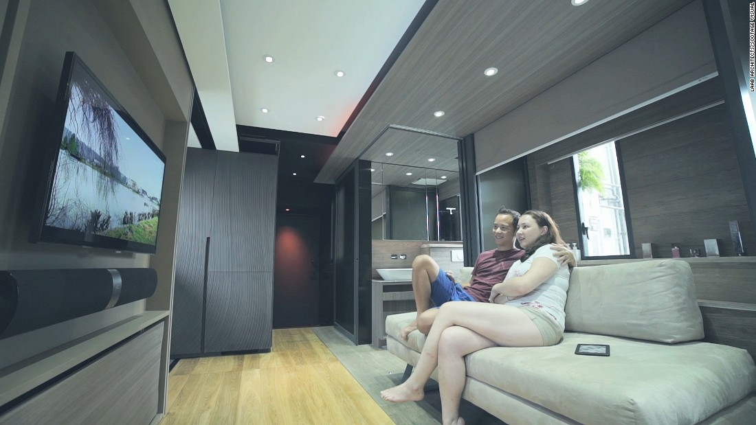 The convertible living room space fits eight people comfortably. The couch transforms into a two-tiered seating area, turning the living room into a home cinema.
