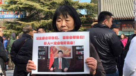 "Dai Shuqin's sister's family of five were on MH370. The piece of paper she holds up reads: ""President Xi will help us! The country will help us. There will be good news about our loved ones."""