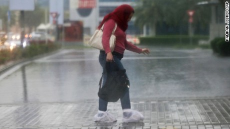 A woman covers her shoes with plastic bags from the rain Wednesday in Dubai.