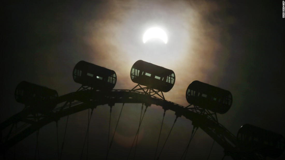 A partial solar eclipse is seen behind passenger capsules of the Singapore Flyer.