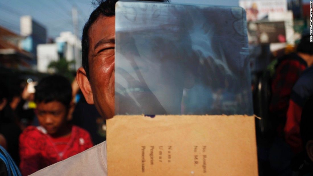 An Indonesian man watches the total solar eclipse using an X-ray film in Yogyakarta, Indonesia.