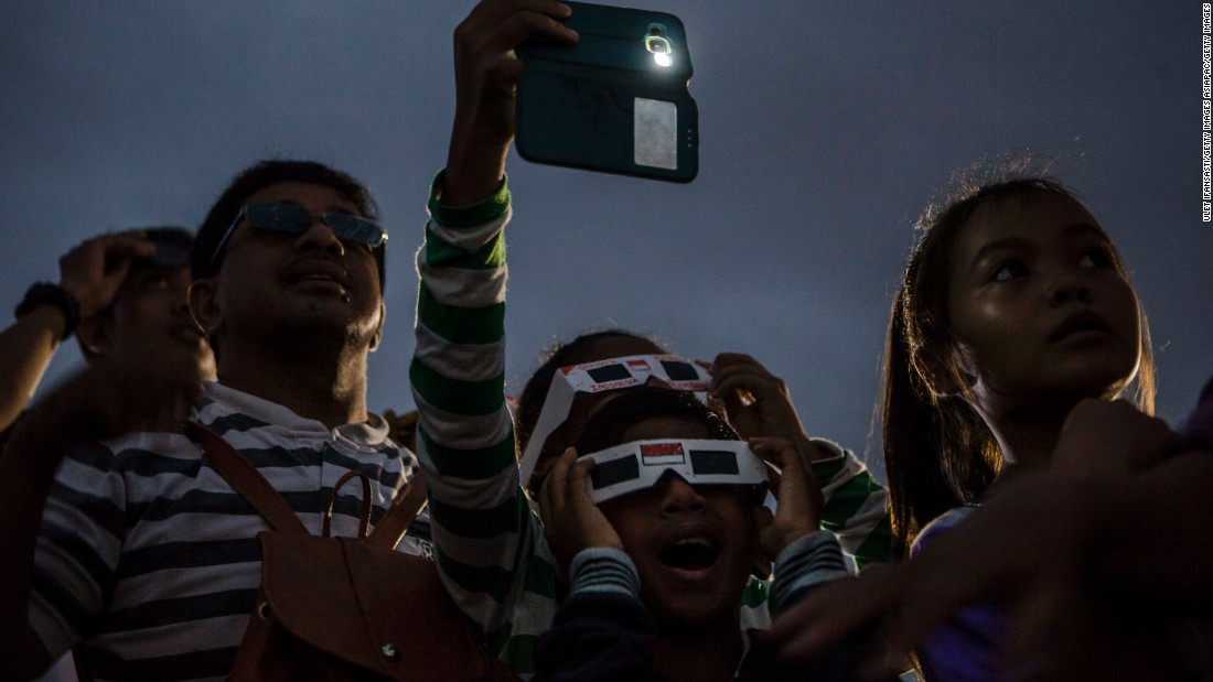 Special filters are needed in order to view the sun safely. Here, a crowd in Palembang city in Indonesia's South Sumatra province gather for the event.