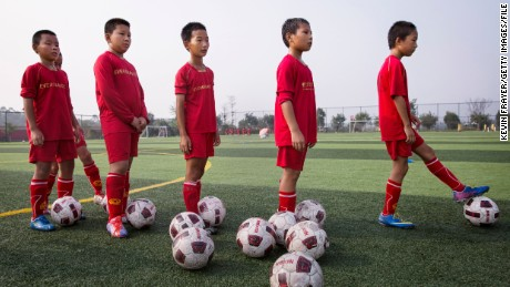 QINGYUAN, CHINA - JUNE 14:  Young Chinese students wait to kick during training at the Evergrande International Football School on June 14, 2014 near Qingyuan in Guangdong Province, China. The sprawling 167-acre campus is the brainchild of property tycoon Xu Jiayin, whose ambition is to train a generation of young athletes to establish China as a football powerhouse. The school is considered the largest football academy in the world with 2400 students, more than 50 pitches and a squad of Spanish coaches through a partnership with Real Madrid. (Photo by Kevin Frayer/Getty Images)