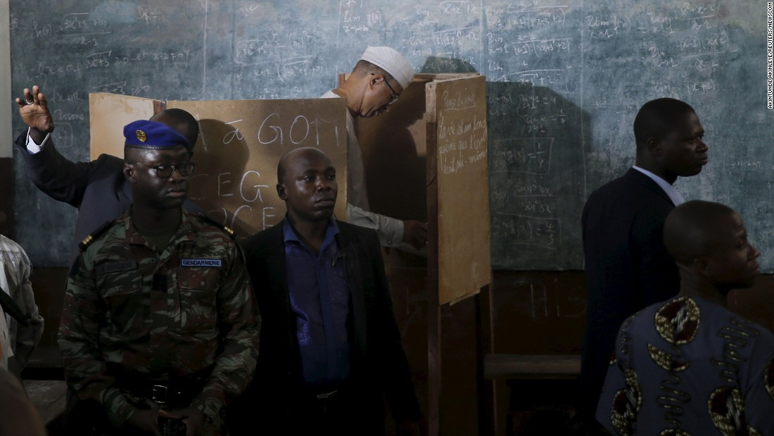 Lionel Zinsou, Benin's Prime Minister and a presidential candidate, is guarded by security personnel as he prepares to cast his vote in Cotonou, Benin, on Sunday, March 6.