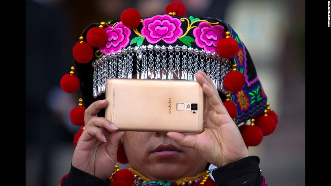 A delegate takes a photo on the steps of Beijing's Great Hall of the People after a plenary session of the National People's Congress on Wednesday, March 9.