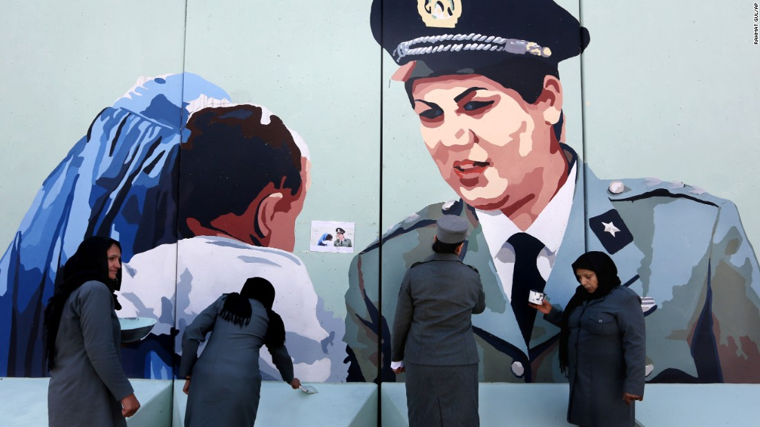 "Police officer Friba Hameed, second from right, helps paint a mural of herself outside the main gate of a police precinct in Kabul, Afghanistan, on <a href=""http://www.cnn.com/2016/03/08/world/gallery/international-womens-day-2016/index.html"" target=""_blank"">International Women's Day,</a> Tuesday, March 8."