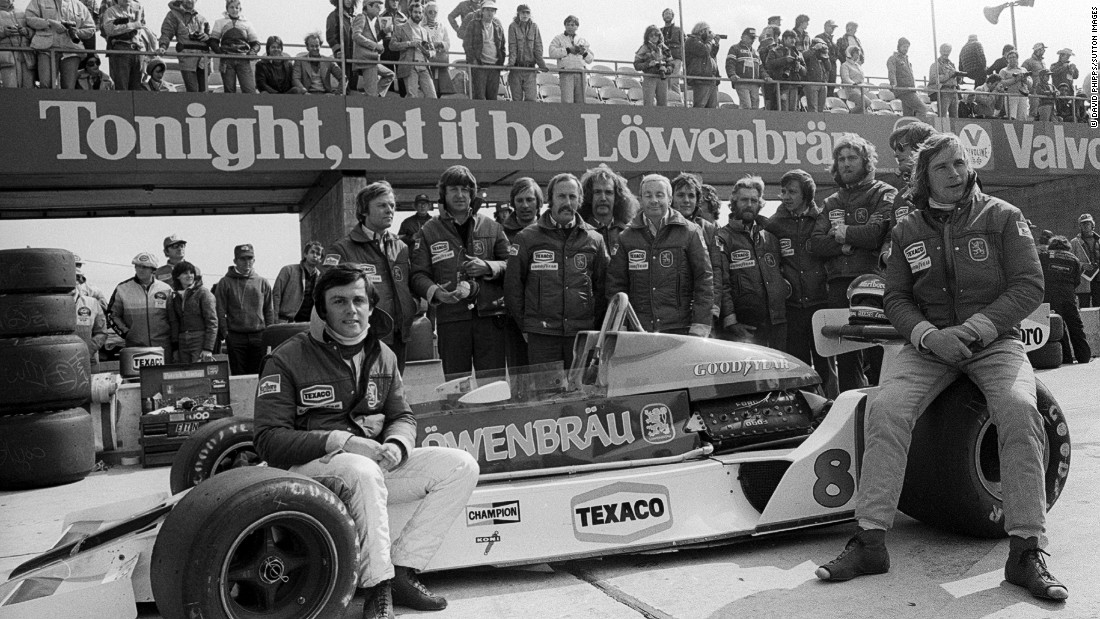 Hunt (right) and French teammate Patrick Tambay (far left) pose with the McLaren M26 car and team at the 1978 United States GP after securing sponsorship from brewer Lowenbrau for the final two races of the season.