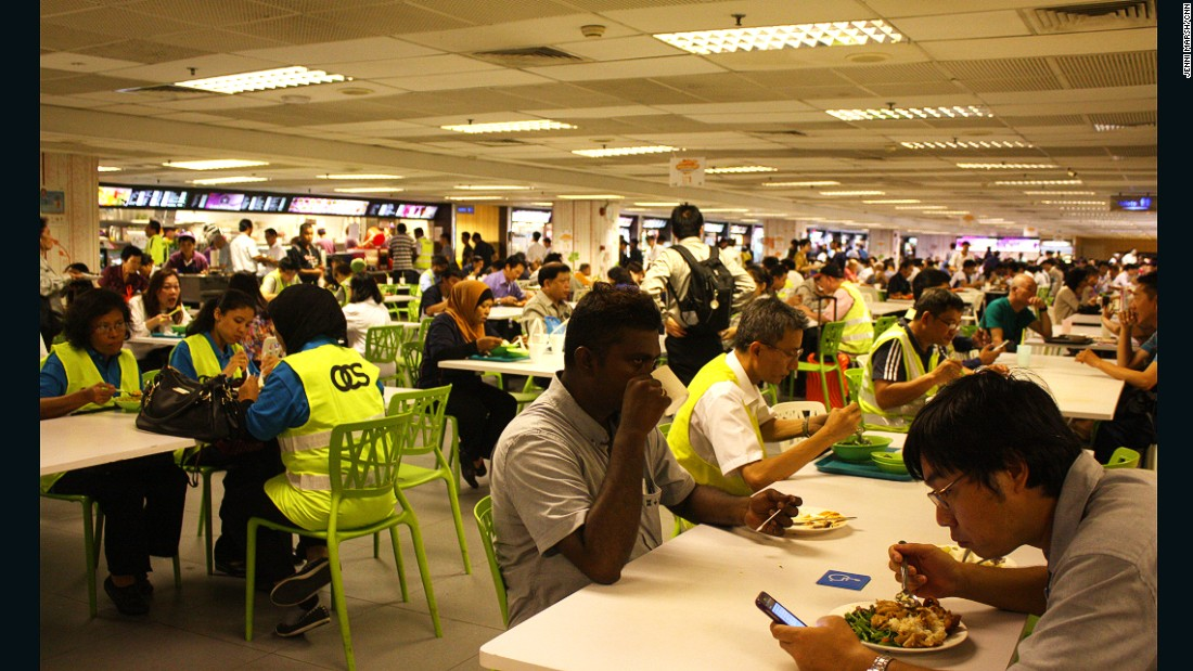 Staff and travelers eat together in the loud and lively food court.