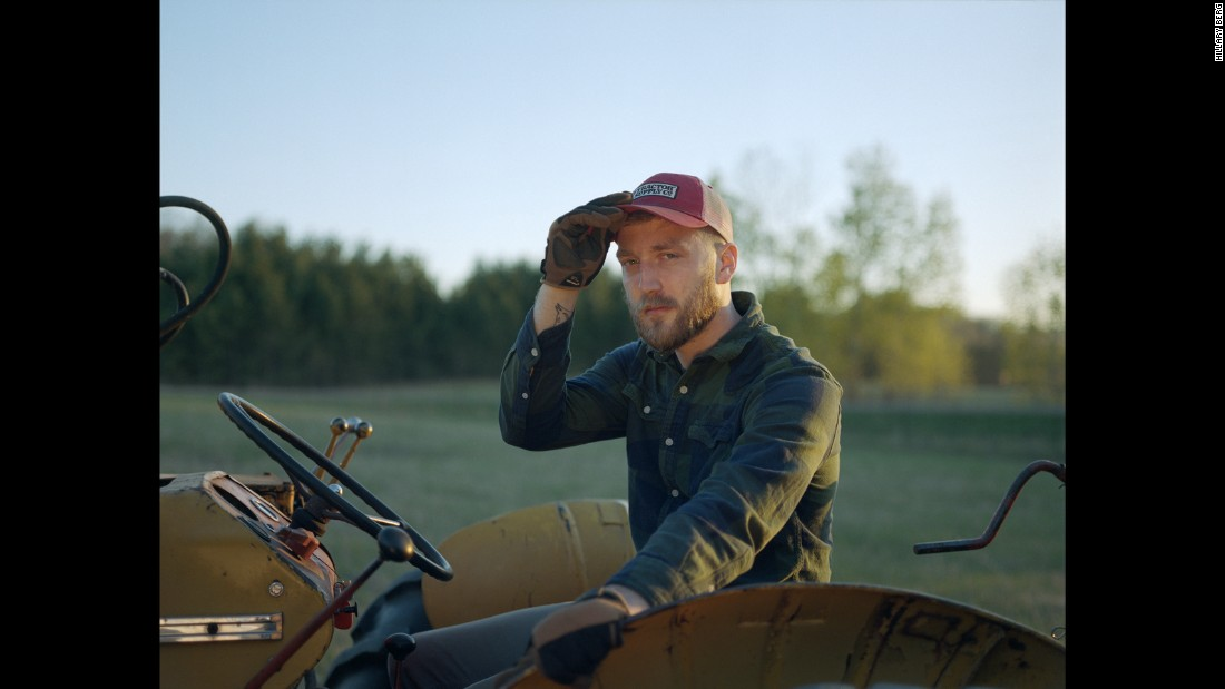 "Wade, the boyfriend of photographer Hillary Berg, sits on an old tractor in Spencer Brook, Minnesota. The couple moved to the rural town two years ago after living in Minneapolis. ""Our home was built in 1900 as one of the original farms in the area,"" Berg said. ""The house now sits on a remaining 12 acres, though the surrounding land is still actively farmed."""