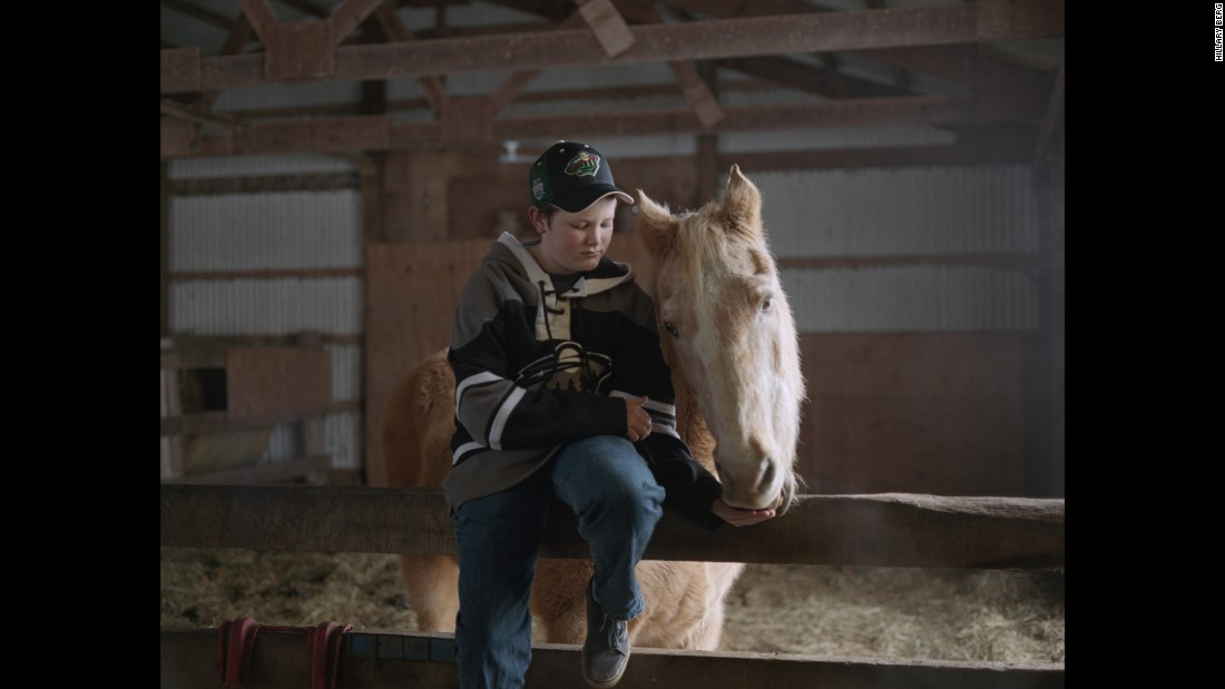 To connect with her new community, Berg photographed its people. Here, a boy feeds his family's horse outside of Cambridge, Minnesota.
