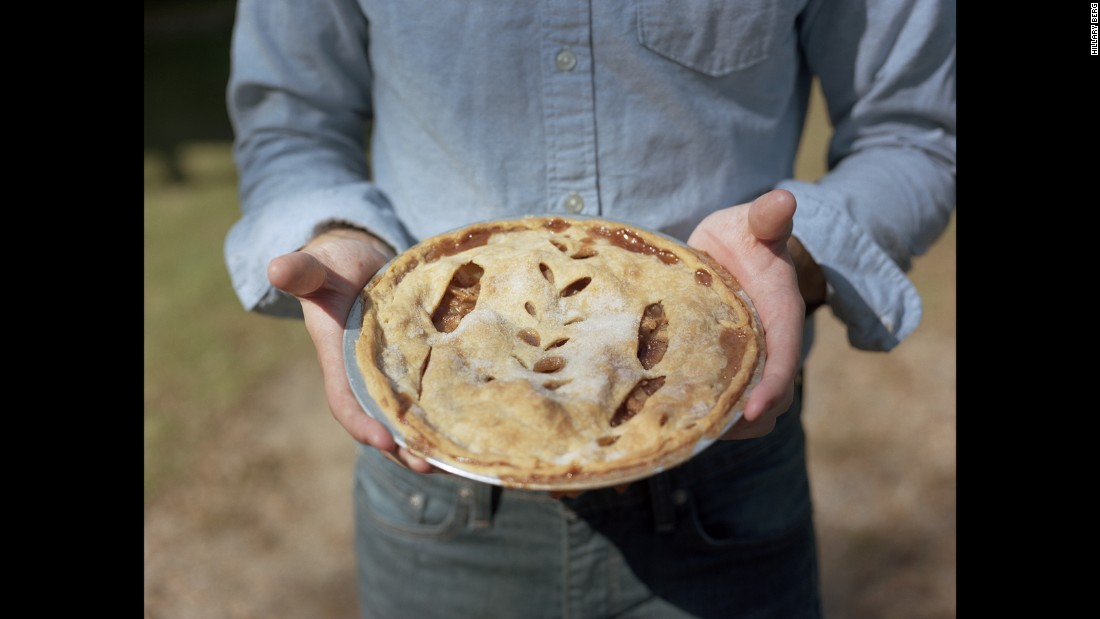 "Wade holds an apple pie from the couple's neighbors, Duane and Dolores. ""The small gestures of sharing recipes, exchanging vegetables from the garden, and moments of small talk in the middle of our gravel road have made the vast space between houses feel less empty over the two years we've lived here,"" Berg said."
