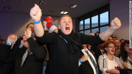 Alternative for Germany (AfD) supporters react after exit poll results are announced on March 13, 2016.