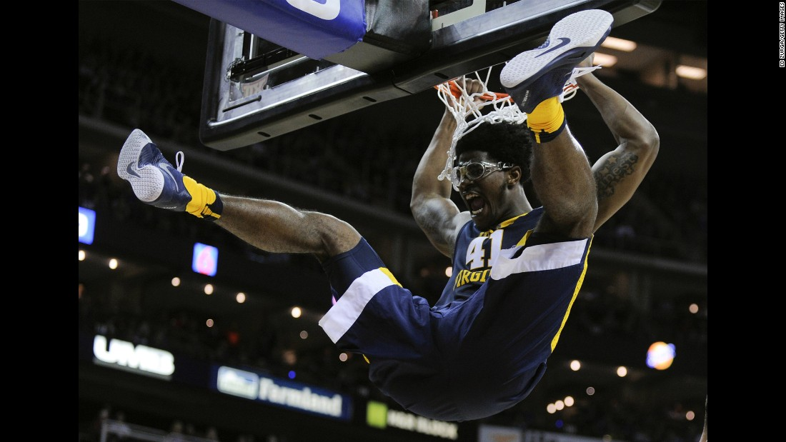 Devin Williams of the West Virginia Mountaineers hangs on the rim after dunking against the Kansas Jayhawks in the first half during the championship game of the Big 12 Basketball Tournament on Saturday, March 12, in Kansas City, Missouri.