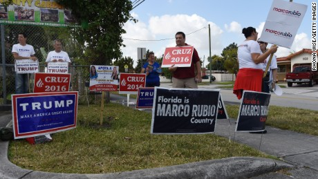 Supporters hold signs for Republican candidates in front of polling precinct for the Florida Primary on March 15, 2016 in Miami, Florida.  Voters began going to the polls Tuesday in five make-or-break presidential nominating contests, with Republican Donald Trump and Democrat Hillary Clinton seeking to tighten their grip as their party's front runners. / AFP / RHONA WISE        (Photo credit should read RHONA WISE/AFP/Getty Images)