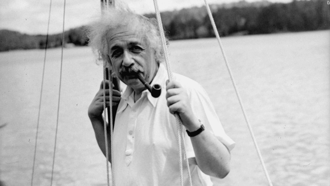 Einstein leans against the mast of a sailboat in Saranac Lake, New York, in 1936.
