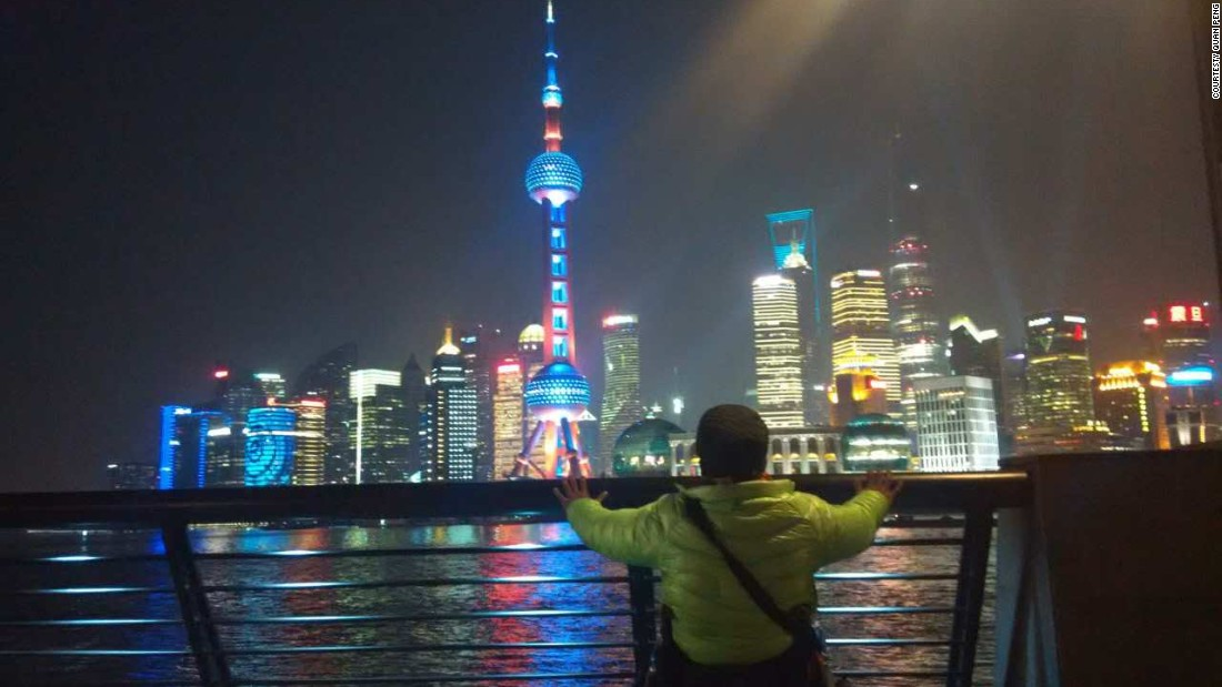 Quan Peng gazes at Shanghai's Pudong financial district across the Huangpu River.