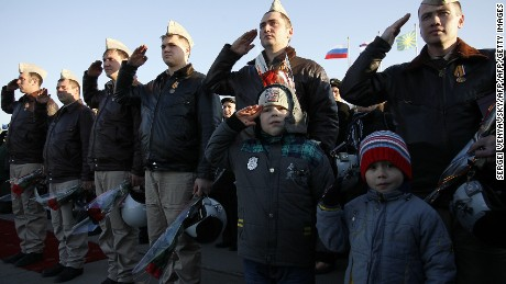 Russian air force pilots salute upon their arrival from Syria at an airbase in the southern Russia's Krasnodar region, on March 16, 2016.