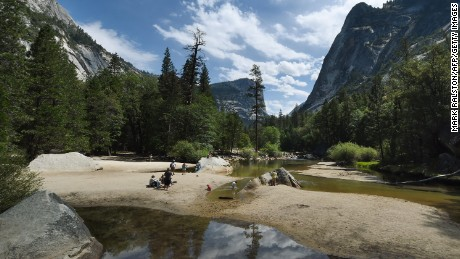 People held picnic on the exposed sandy bottom of Mirror Lake that is normally underwater and used by visitors to photograph reflections of the Half Dome rock monolith at Yosemite National Park in California on June 4, 2015.