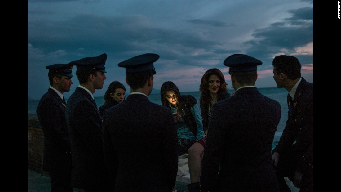 "Cadets flirt at dusk in Naples, Italy. Giulio Rimondi took a two-year journey across his Italian homeland, photographing private moments and beautiful landscapes. He traveled north, east, west and south. ""I basically got lost,"" he said."