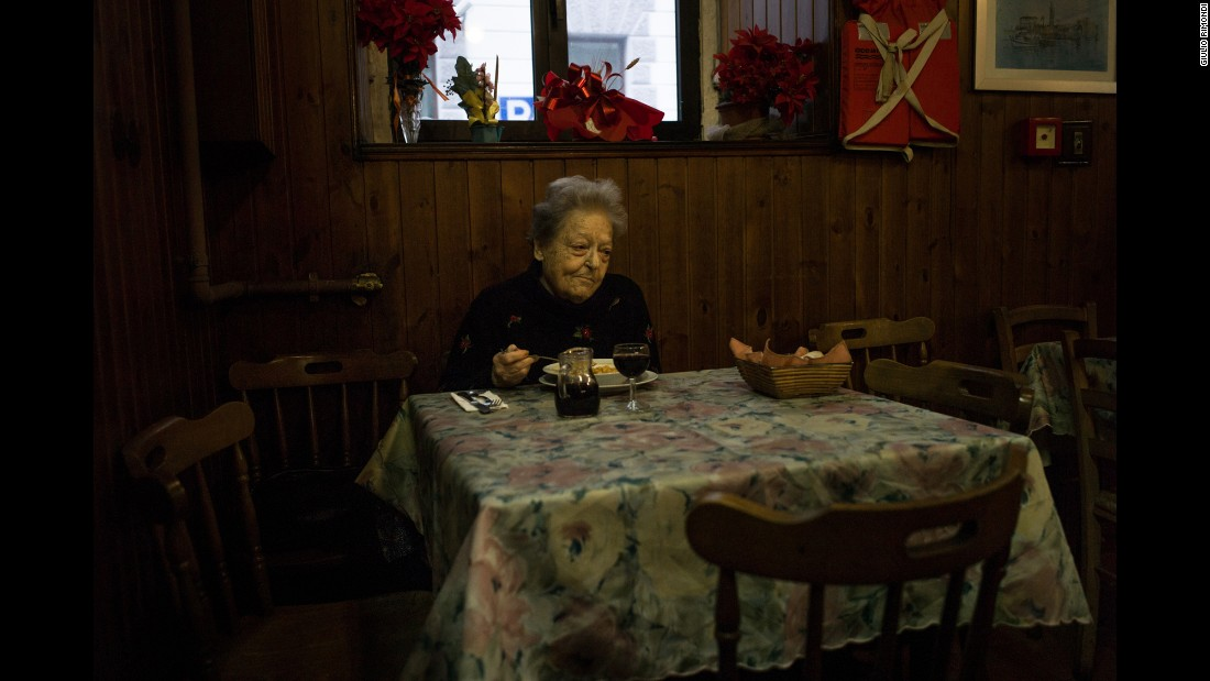 "A retired professor has a meal in Trieste, Italy. Rimondi said he never asks permission to take any of his photos. ""I take two or three photos without being noticed ... something happens ... and that is when you take the picture,"" he said. ""That is the moment of the picture."""