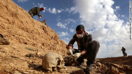 An Iraqi man inspects on February 3, 2015, the remains of members of the Yazidi minority killed by the Islamic State (IS) jihadist group after Kurdish forces discovered a mass grave near the village of Sinuni, in the northwestern Sinjar area. (SAFIN HAMED/AFP/Getty Images)