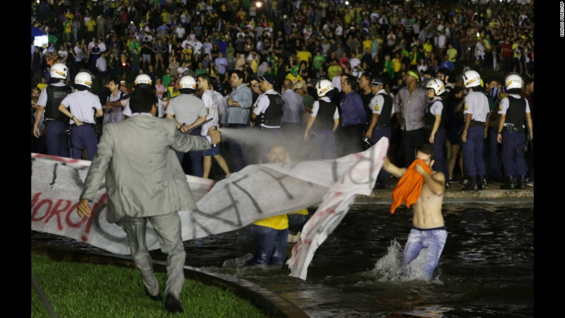 A police officer uses pepper spray on protesters to keep them from getting closer to the Congress building in Brasilia on March 16.