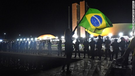 A woman waves a Brazilian national flag in front of a line of riot policemen during a protest against corruption in front of the Congress building in Brasilia on Wednesday, March 16, 2016. President Dilma Rousseff named her predecessor Luiz Inacio Lula da Silva as her chief of staff, sparing him possible arrest for corruption as she seeks to fend off a damaging crisis.