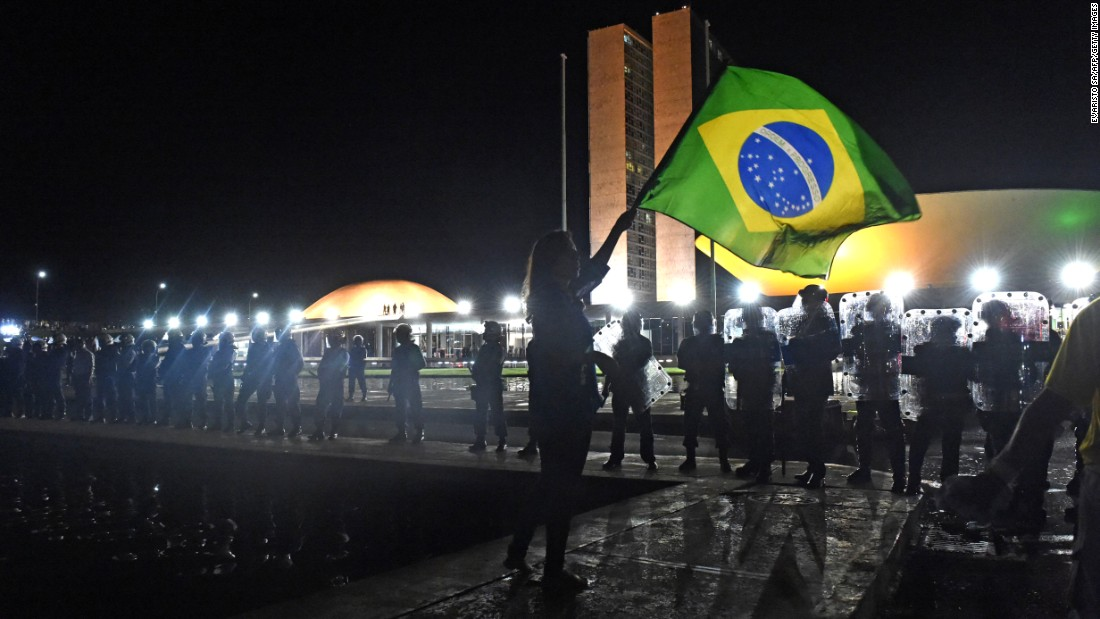 A woman waves a Brazilian national flag in front of a line of riot policemen in Brasilia on March 16.