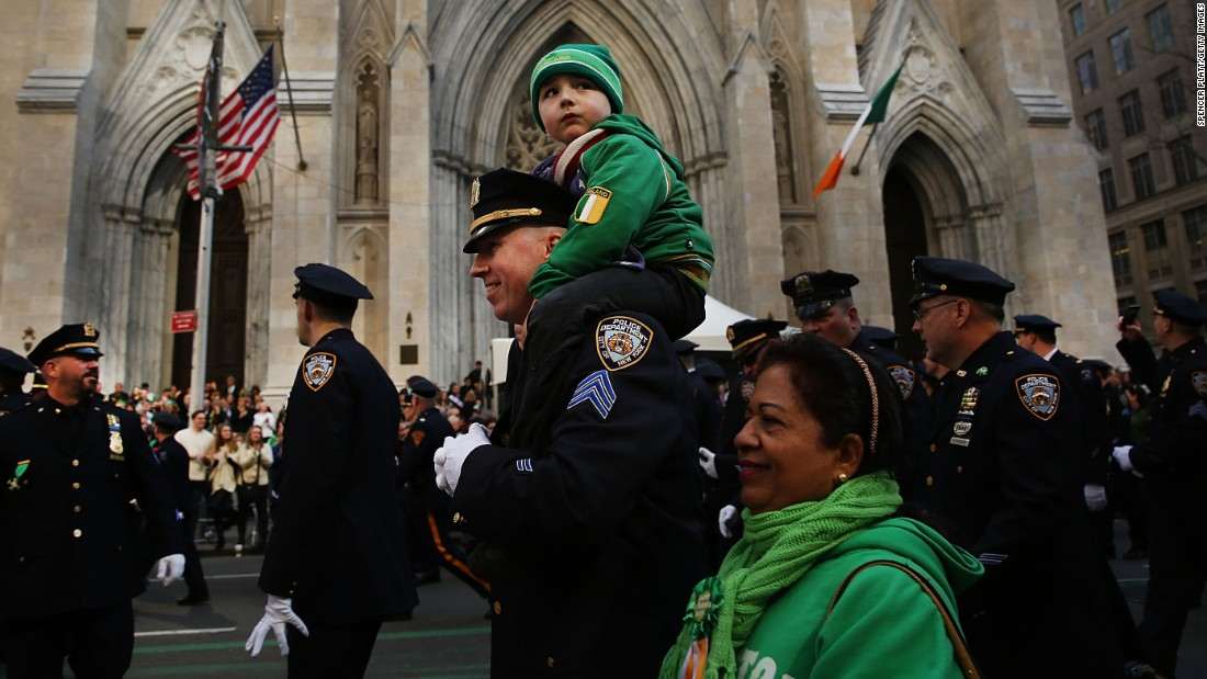 A police officer marches with his son in New York's parade.