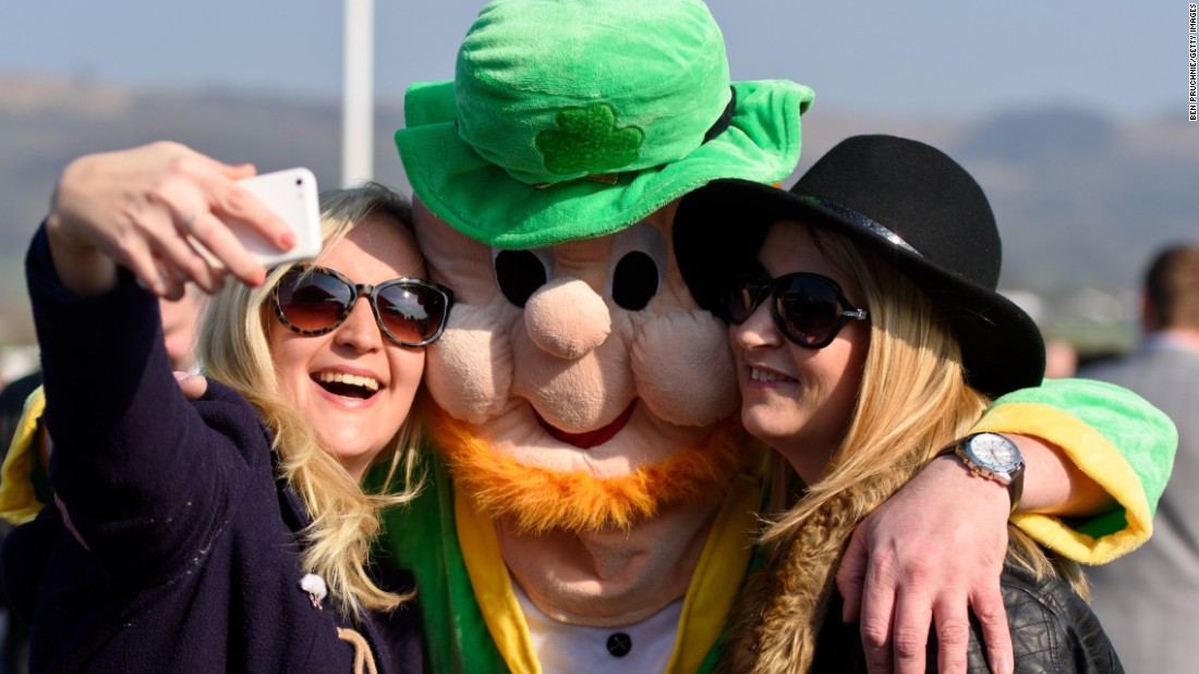 A man wearing a leprechaun costume poses for a selfie during the Cheltenham Festival in Cheltenham, England.