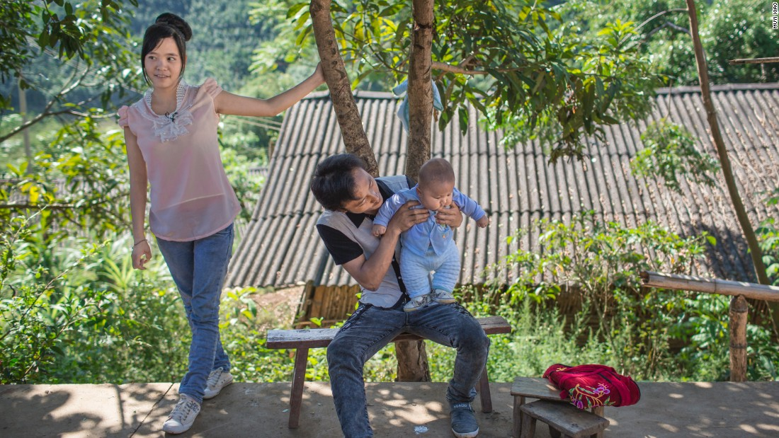 Xiao Rong, 16, (left) looks on as her 20-year-old husband Xiao Yong holds their 10-month-old baby, in Mengla county, Yunnan province.