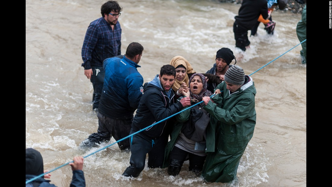 "Migrants try to cross a river after leaving a refugee camp in Idomeni, Greece, on Monday, March 14. As many as 14,000 migrants <a href=""http://www.cnn.com/2016/03/10/europe/europe-migrant-crisis/"" target=""_blank"">were stranded in dire conditions</a> after Macedonia closed its doors to refugees."
