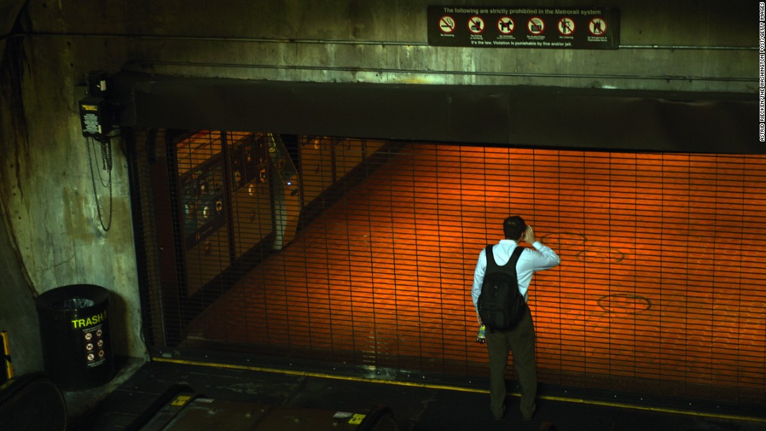 "A commuter looks through the closed gate of a Metro station in Washington on Wednesday, March 16. The rail system <a href=""http://www.cnn.com/2016/03/15/us/washington-metrorail-shutdown/index.html"" target=""_blank"">was temporarily shut down for safety inspections,</a> officials said, two days after an electrical fire in a Metro tunnel."