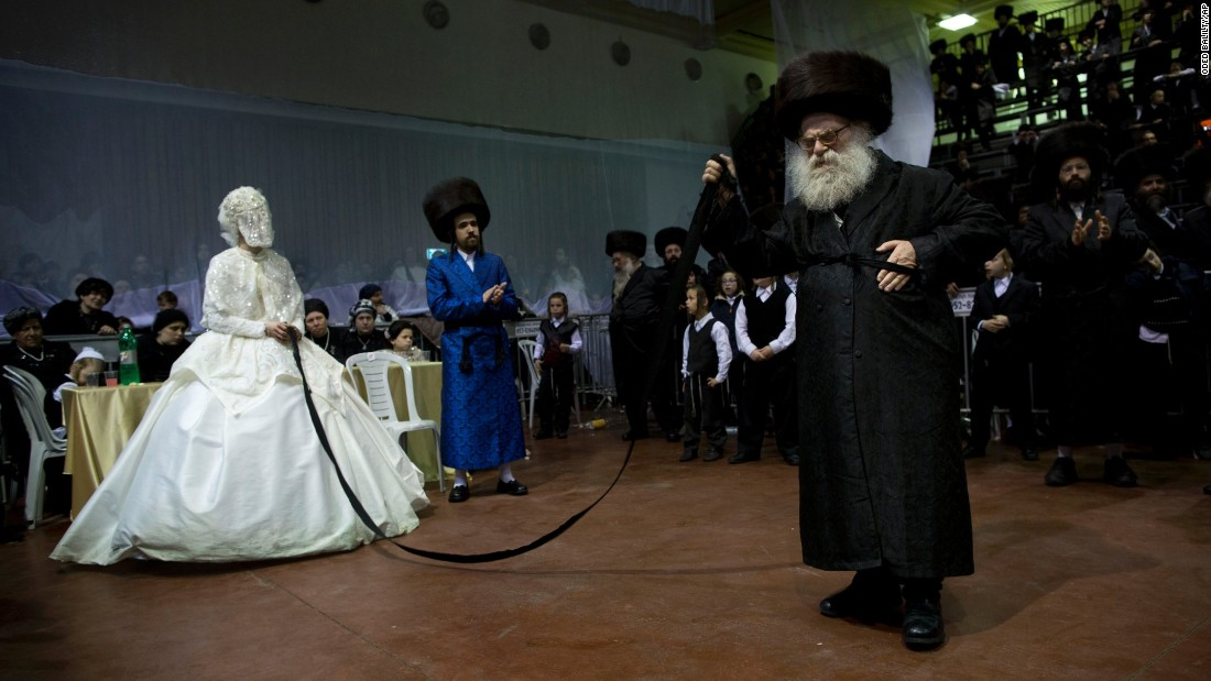 An ultra-Orthodox Jewish bride enters the men's section of her wedding to fulfill the Mitzvah tantz -- where family members and honored rabbis are invited to dance in front of the bride -- in Netanya, Israel, on Wednesday, March 16.
