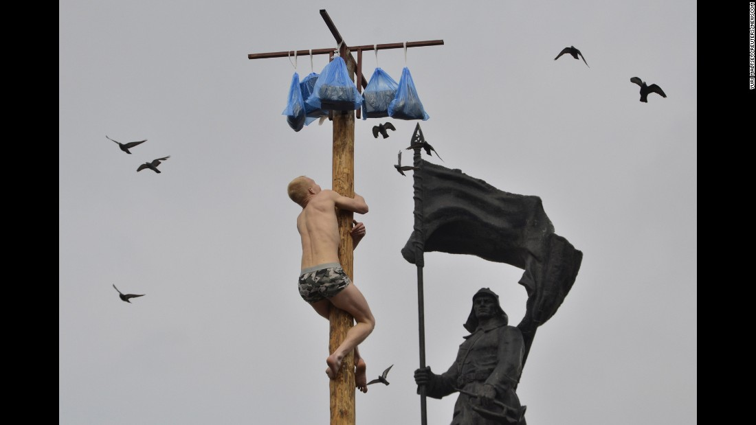 A man tries to climb a wooden pole to get a prize during Maslenitsa celebrations in Vladivostok, Russia, on Sunday, March 13. Maslenitsa, a holiday marking the end of winter, is traditionally celebrated with pancake eating and feats of strength.