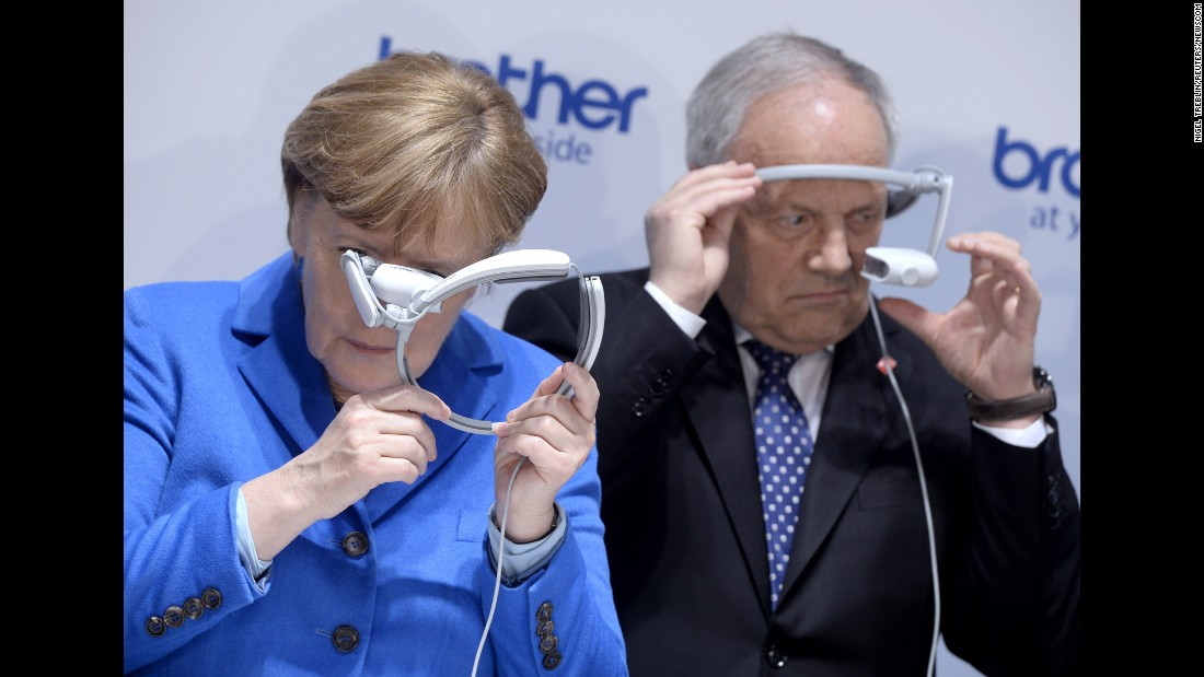 German Chancellor Angela Merkel and Swiss President Johann Schneider-Ammann look at head-mounted display units during an electronics fair in Hanover, Germany, on Tuesday, March 15.